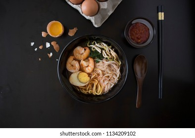 Penang Laksa Noodle Soup flat lay with ingredients on a black table. Malaysian Assam Laksa on a dark wooden table with ingredients spread on the table.