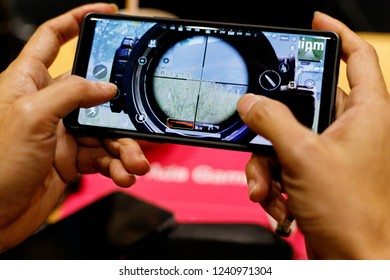 PENANG, MALAYSIA - 11 NOV 2018: Close up gamer hand holding a smartphone with Player's Unknown Battleground also known as PUBG online shooting gaming. It is an online multiplayer battle game.