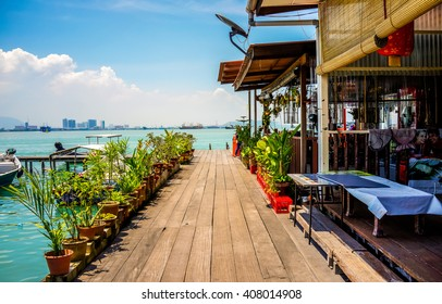 Penang, Malaysia - 12 August 2015: A wooden plank walkway along with a restaurant on the Chew Jetty fishing village in Penang, Malaysia.