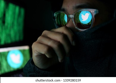 PENANG, MALAYSIA - 14 MARCH 2019: Twitter security and privacy issues. Hacker with computer hacking and stealing data information, Twitter logo and binary code as background.