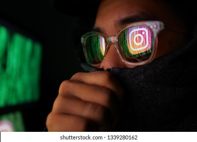 PENANG, MALAYSIA - 14 MARCH 2019: Instagram security and privacy issues. Hacker with computer hacking and stealing data information, Instagram logo and binary code as background