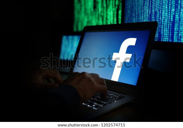 PENANG, MALAYSIA - 14 OCT 2018: Facebook security and privacy issues. Hacker with computer hacking and stealing data information, Facebook logo and binary code as background.