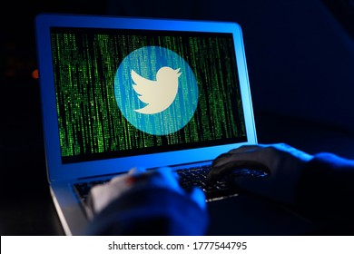 PENANG, MALAYSIA - 16 JULY 2020: Hacker with computer hacking and stealing data information, Twitter logo and binary code as background. Twitter security and privacy issues.