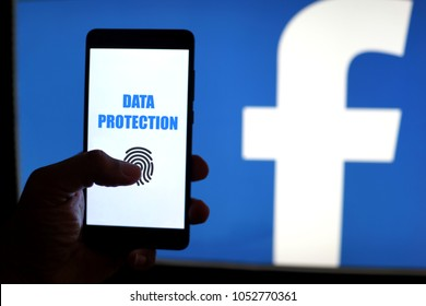 PENANG, MALAYSIA - 22 MARCH 2018: Facebook security and privacy issues. Close up man scanning fingerprint on smartphone to get access data information with Facebook logo as background