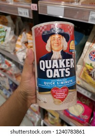 Penang, Malaysia - 23 November 2018 : Hand hold a container of QUAKER OATS Quick 1-Minute for sell in the supermarket.
