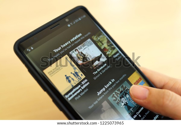 PENANG, MALAYSIA - 25 OCT 2018: Close up woman holding Smartphone and using Spotify application on the screen. Spotify is a music streaming platform developed by Swedish company Spotify Technology.