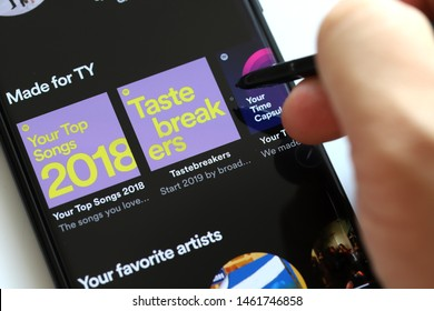 PENANG, MALAYSIA - 26 JULY 2019: Close up user browsing Smartphone and using Spotify application on the screen. Spotify is a music streaming platform developed by Swedish company Spotify Technology.