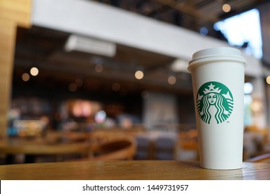 PENANG, MALAYSIA - 27 JUNE 2019: Starbucks take away coffee cup with logo, bokeh interior background. Starbucks is the world's largest coffee house with over 20,000 stores in 61 countries.