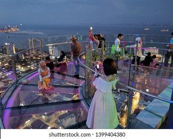 Penang, Malaysia - 30 MARCH 2019 : A group of tourists taking photo and posing at Rainbow skywalk, a tourist attraction at The Top, KOMTAR.