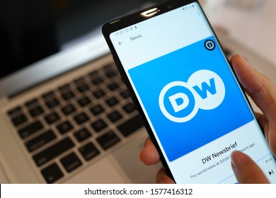 PENANG, MALAYSIA - 9 OCT 2019: Man listening DW NEWS broadcasting on an Android phone. DW News is a global English-language news and information channel from a German international broadcaster.