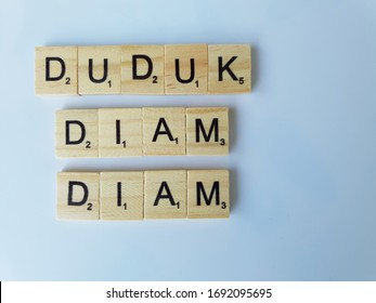 """Penang, Malaysia - April 1, 2020: Scrabble game letters on white background. Words """"DUDUK DIAM DIAM"""" on scrabble alphabet tiles. Word in Malay languages (Translate - Stay Home)."""