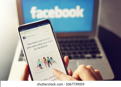 PENANG, MALAYSIA - April 13 2018: Facebook security issues. Facebook Privacy Basics page displayed on the mobile phone screen in female hands. Laptop with Facebook logo as background.