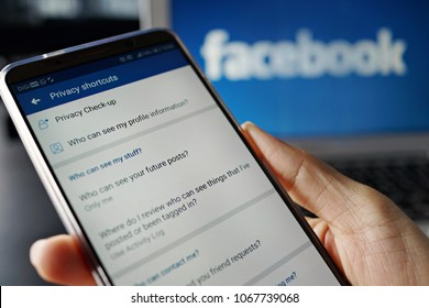 PENANG, MALAYSIA - April 13 2018: Facebook security and privacy issues. Facebook Privacy Shortcuts page displayed on the mobile phone screen in female hands. Laptop with Facebook logo as background.