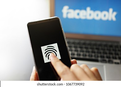 PENANG, MALAYSIA - April 13 2018: Facebook security and privacy issues. Close up female scanning fingerprint on smartphone to get access data information with Facebook logo on laptop as background.