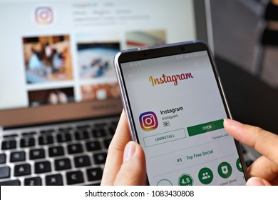 PENANG, MALAYSIA - April 13 2018: Woman hand holding smartphone with social internet service Instagram application on the screen. Laptop with Instagram page on background.