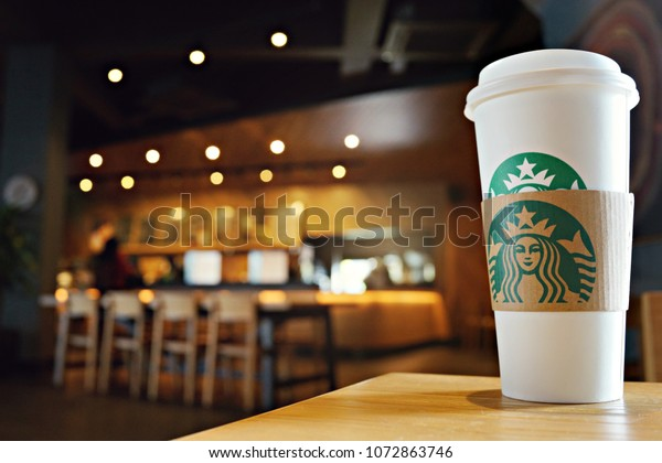 Penang, Malaysia - April 13, 2018 : Close up Starbuck hot coffee cup with blur Starbuck interior for background.