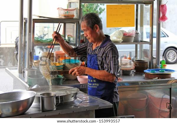 PENANG, MALAYSIA - APRIL 2012 : A man making noodles at noodle stall on Lorong Kampung Malabar street, Penang, Malaysia on April 18, 2012. Noodle soup is one of the most popular street foods in Penang