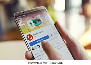 Penang, Malaysia - April 3, 2019: Hand holding a smartphone with Sign up Shutterstock account on Facebook page. Blurred cafe interior on background.