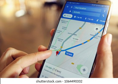 Penang, Malaysia - April 6, 2018: A female is using Google Maps service on smartphone at cafe. Google Maps is most popular mapping service for mobile provided by Google.