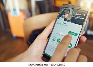 Penang, Malaysia - April 6, 2018: A female is using Grab application on smartphone at cafe. Grab is a Malaysian technology company that offers ride-hailing and logistics services through its app.