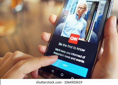 PENANG, MALAYSIA - April 6 2018: Woman holding smartphone with CNN homepage on the screen. CNN was the first television channel to provide 24-hour news coverage