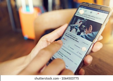 PENANG, MALAYSIA - April 6 2018: Woman holding smartphone with social Internet service Facebook on the screen. Blurred cafe interior on a background.