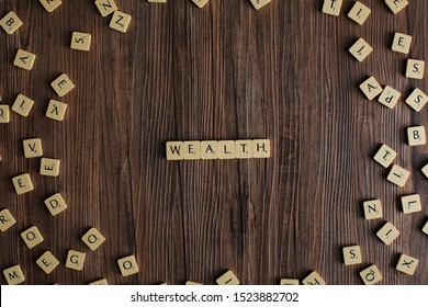 Penang, Malaysia. Aug 12, 2019. The word 'Wealth' spelled out with scrabble, isolated on wooden background, presentation background, tax concept, finance concept - Image