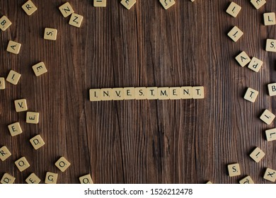 Penang, Malaysia - Aug 12, 2019. 'Invest' spelled out with scrabble tiles, isolated on loose scrabble tiles against wooden background, invest concept, finance concept, presentation background - Image