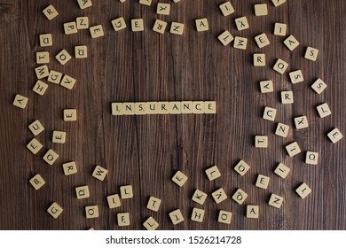 Penang, Malaysia - Aug 12, 2019: 'Insurance' spelled out with scrabble tiles, isolated on loose scrabble tiles against wooden background, insurance concept, presentation background - Image