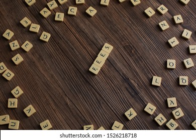 Penang, Malaysia - Aug 12, 2019. 'Fees' spelled out with scrabble tiles, isolated on loose scrabble tiles against wooden background, fees concept, finance concept, presentation background - Image