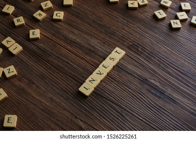 Penang, Malaysia - Aug 12, 2019: 'Invest' spelled out with scrabble tiles, isolated on loose scrabble tiles against wooden background, invest concept, finance concept, presentation background - Image