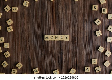 Penang, Malaysia - Aug 12, 2019. 'Money' spelled out with scrabble tiles, isolated on loose scrabble tiles against wooden background, money concept, currency concept, presentation background - Image