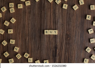 Penang, Malaysia - Aug 12, 2019: 'Buy' spelled out with scrabble tiles, isolated on loose scrabble tiles against wooden background, buying concept, finance concept, presentation background - Image