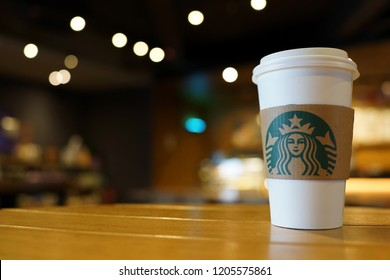 PENANG, MALAYSIA - AUG 28, 2018: Starbucks take away coffee cup with logo on sleeve, bokeh interior background. Starbucks is the world's largest coffee house with over 20,000 stores in 61 countries.