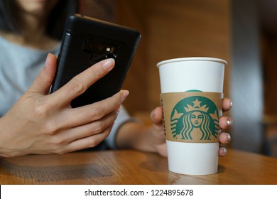 PENANG, MALAYSIA - AUG 28, 2018: Female hand holding a Starbucks coffee cup and using smartphone indoor. Starbucks is the world's largest coffee house with over 20,000 stores in 61 countries.