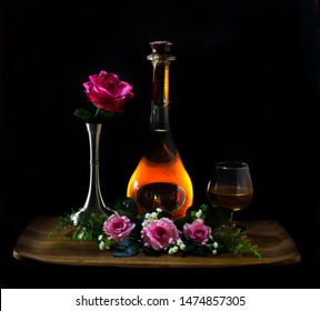 PENANG, MALAYSIA - AUGUST 10, 2019: Romantic setting of a bottle of Otard brandy whisky cognac with glasses and red pink roses and pewter vase on teak wooden tray on dark black background.