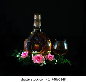 PENANG, MALAYSIA - AUGUST 10, 2019: Romantic setting of a bottle of Swing whisky brandy cognac with glasses and red pink roses and pewter vase on dark black background.