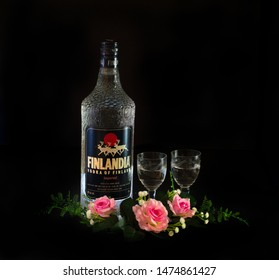 PENANG, MALAYSIA - AUGUST 10, 2019: Romantic setting of a bottle of Finlandia vodka whisky cognac with glasses and red pink roses and pewter vase on dark black background.