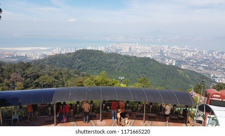 Penang, Malaysia- August 13,2018 : Tourists and locals are on Penang hill to watch a Panoramic view of Penang city (Georgetown). Buildings, mountain, ocean,while cloud and blue sky. Penang, Malaysia.