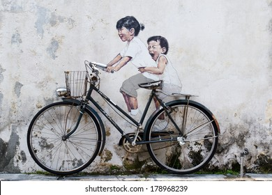 PENANG, MALAYSIA - AUGUST 16: Street Mural Installation Painting tittle 'Little Children on a Bicycle' painted by Ernest Zacharevic in Penang on August 16, 2013.