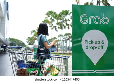 PENANG, MALAYSIA - AUGUST 27, 2018 : Passenger is waiting for Grab car at pick up location. Grab is a Singapore based company that offers ride-hailing and logistics services through its app.