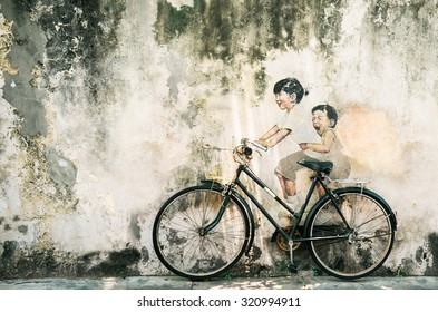 PENANG, MALAYSIA - August 29: Street Mural entitled 'LIttle Children on a Bicycle' is one of the 9 murals painted by Ernest Zacharevic in early 2012. Picture taken on August 29, 2015.