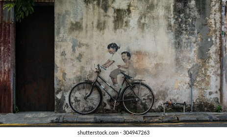 PENANG, MALAYSIA - AUGUST 5, 2014: Street Mural tittle 'Little Children on a Bicycle' painted by Ernest Zacharevic in Penang on Feb.14, 2012.