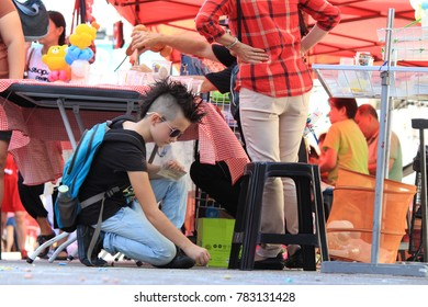 PENANG, MALAYSIA- Dec 24, 2017 : A young toddler was squatting down on the ground doing floor painting at Occupy Beach Street event in Georgetown, UNESCO World Heritage site, Penang island, Malaysia.