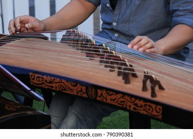 PENANG, MALAYSIA- Dec 24, 2017 :  The street performer is playing the traditional Guzheng (a.k.a. Chinese zither) at Occupy Beach Street in Georgetown, UNESCO World Heritage site, Penang, Malaysia.