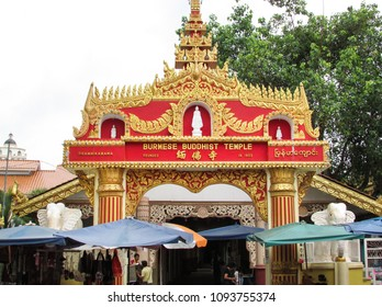 PENANG, MALAYSIA - DECEMBER 09, 2013: decorated entrance to a popular Dhammikarama Burmese Temple surrounded with local shops and people