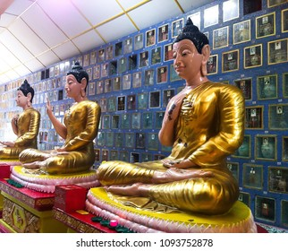 PENANG, MALAYSIA - DECEMBER 10, 2013: three buddha statues in golden dresses, holding different hand positions, placed side by side in famous Wat Chaiyamangalaram Thai buddhist temple