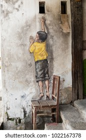 PENANG, MALAYSIA, December 19 2017: Street art titled Reaching Up by Ernest Zacharevic in Georgetown