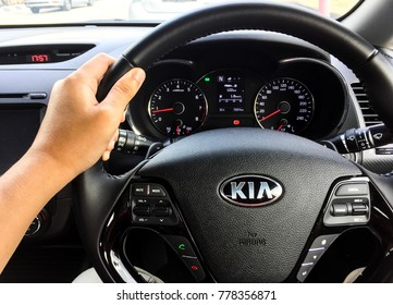 PENANG, MALAYSIA- DECEMBER 20, 2017: Hand holding steering wheel of KIA cerato. Kia Motor Corporation, headquartered in Seoul, is South Korea's second-largest automobile manufacturer.