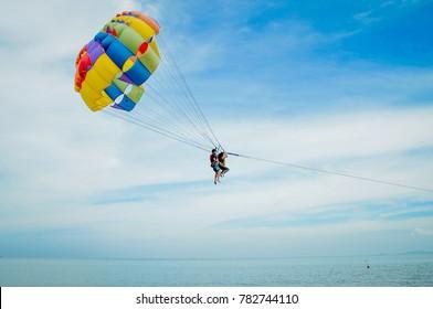 PENANG , MALAYSIA - DECEMBER 25, 2017 : Tourists parasailing in the blue sky  in Penang Island Beach.